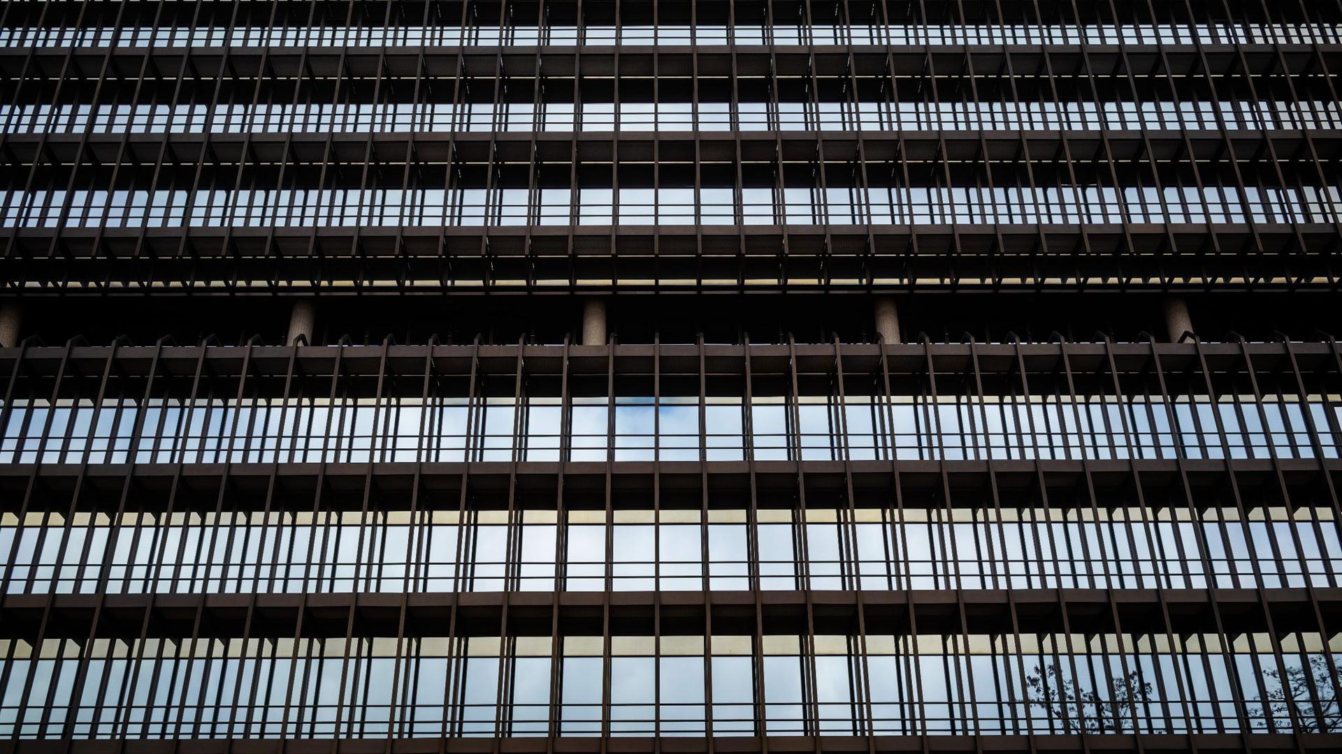 Der Himmel spiegelt sich auf der Fassade aus Glas und Stahl des Deutschen Patentamts in München.