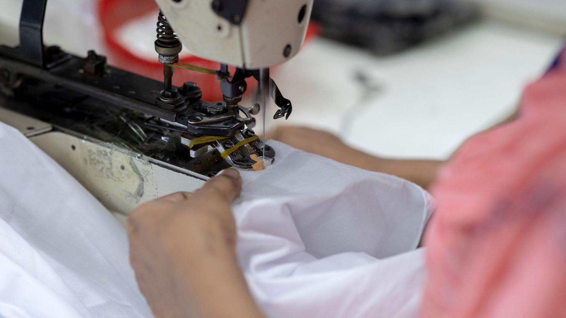 Eine Frau arbeitet in einer Textilfabrik.