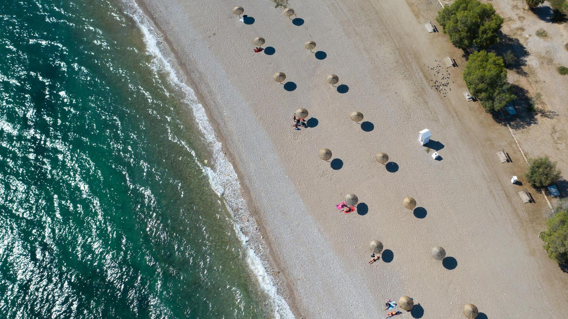An einem Strand südlich von Athen stehen Sonnenschirme für Strandbesucher bereit.