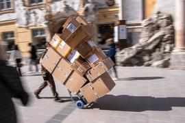 Ein Paketzulieferer transportiert mit einer Sackkarre mehrere Pakete durch die Fußgängerzone.