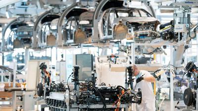 Ein Mitarbeiter arbeitet an der Karosserie eines E-Autos. Die Verdopplung der Rohstoffkosten und fehlende Elektronikchips bremsen derzeit die Autoindustrie aus.