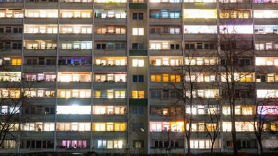 In einem Hochhaus sind einige Fenster beleuchtet.