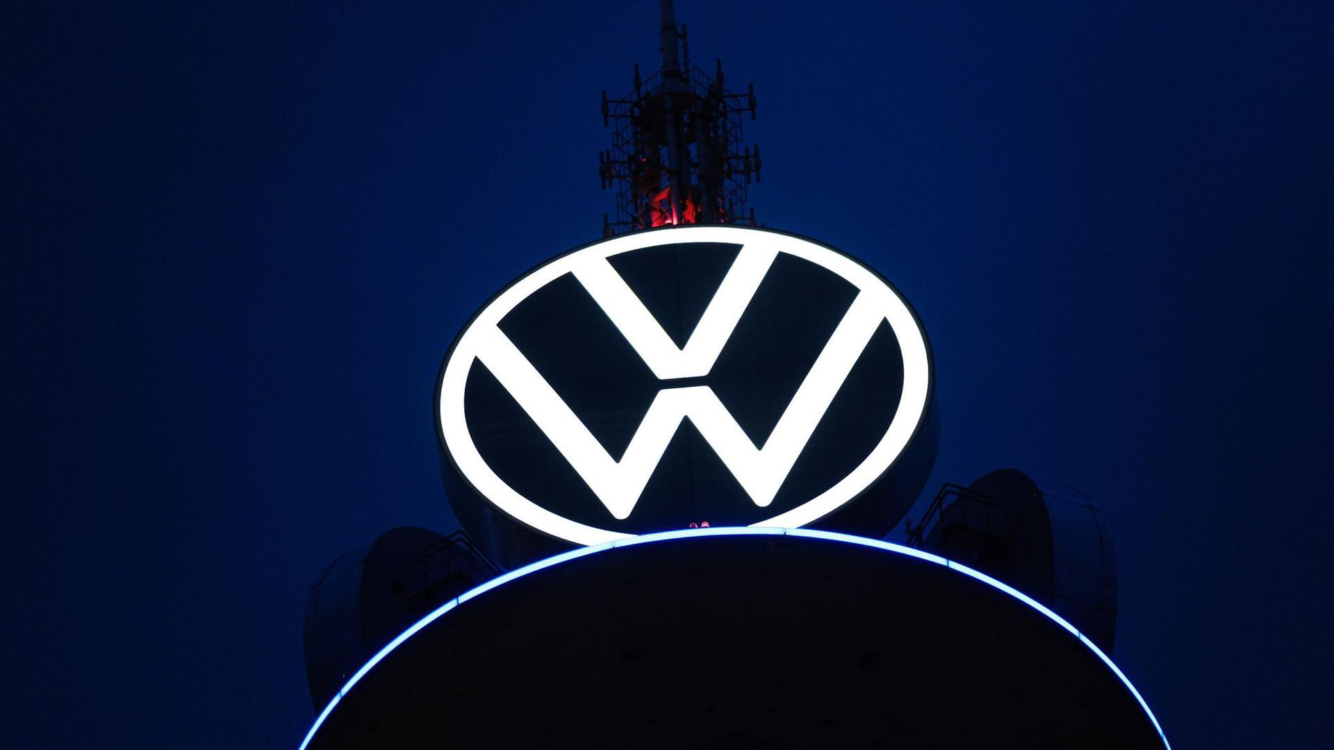 Das Volkswagen Logo leuchtet auf dem VW-Tower vor dunklem Himmel.