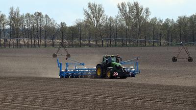 Ein Landwirt fährt mit dem Traktor und angehängter Maislegemaschine über das Feld.