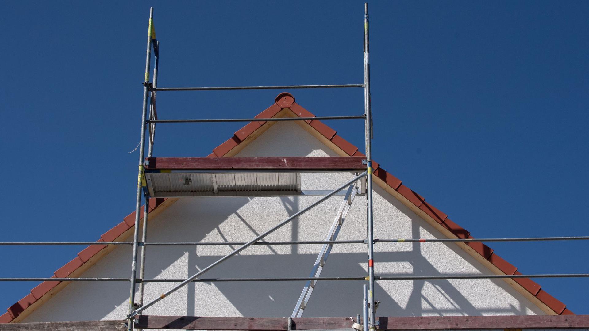 Gerüste stehen an einem Haus einer Neubausiedlung im Frankfurter Stadtteil Nieder-Erlenbach.