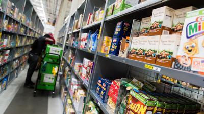 Ein Mitarbeiter eines Lebensmittellieferdienstes packt bestellte Waren ein.