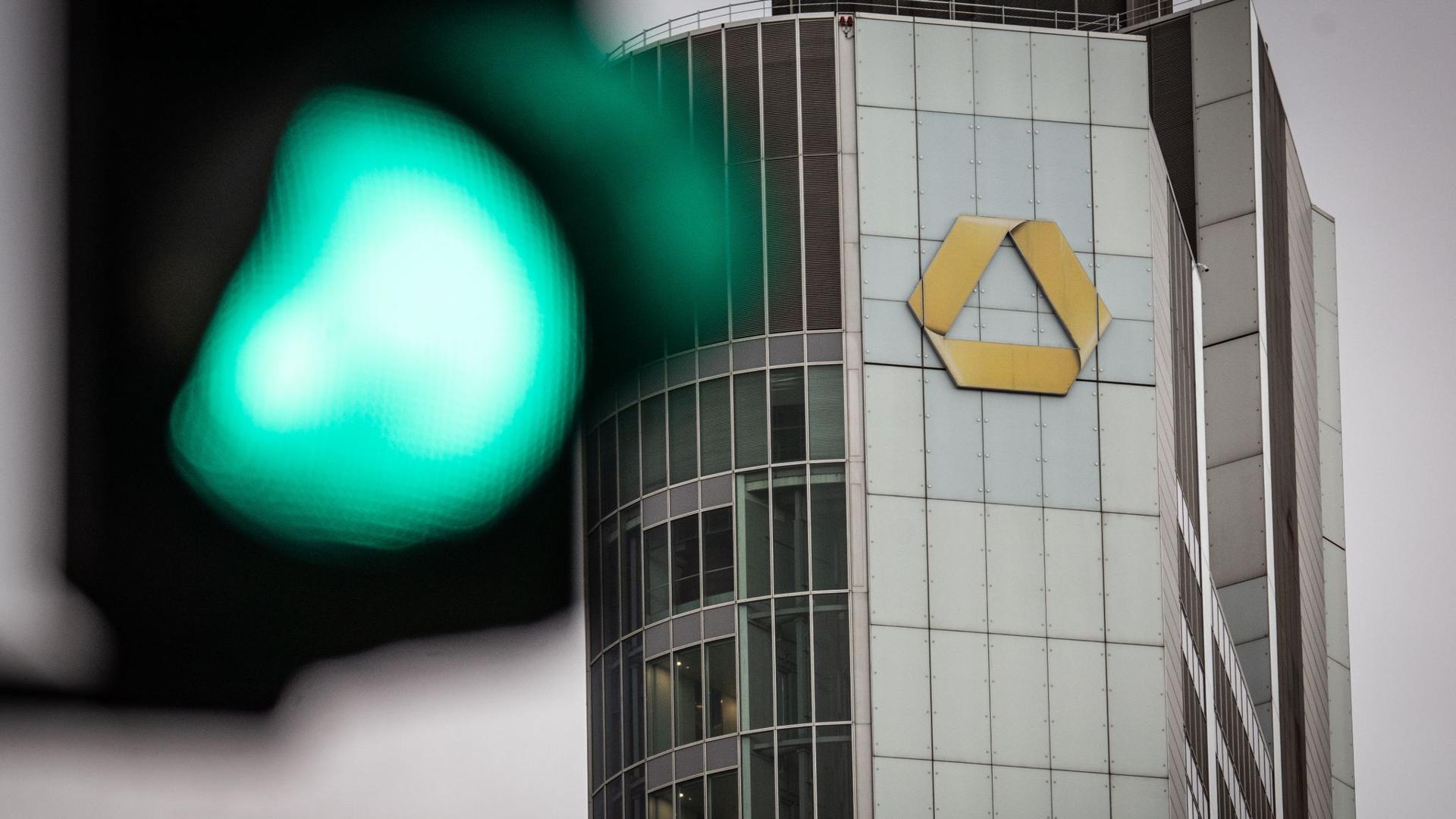Eine Ampel steht auf Grün vor dem Logo an der Zentrale der Commerzbank.