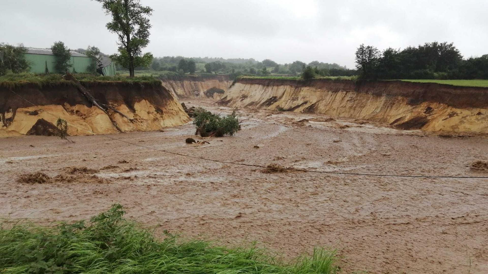 Der vor einigen Jahren wegen des Tagebaus umgelegte Fluss Inde hat sich nach schweren Regenfällen ein neues Bett gegraben und strömt unkontrolliert in den Braunkohle-Tagebau Inden. )