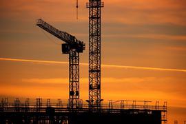 Baukräne einer Großbaustelle bei Sonnenaufgang. Die Stimmung in der Wirtschaft hat sich im Juli überraschend eingetrübt.