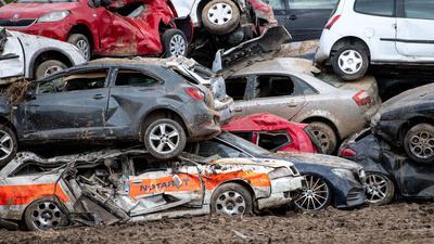 Beim Unwetter zerstörte Autos sind in Bad Neuenahr-Ahrweiler auf einem provisorischen Schrottplatz gestapelt.