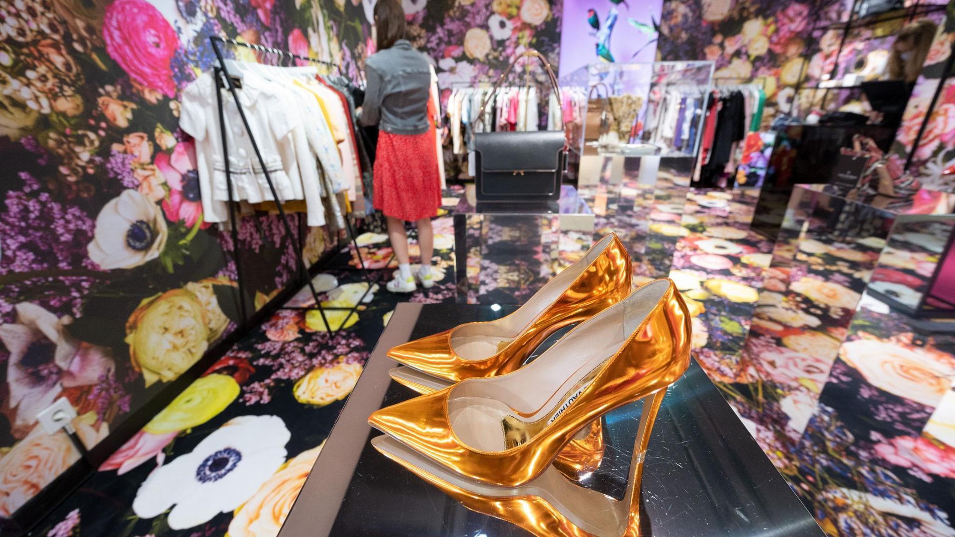 Eine Frau stöbert in einem Secondhand-Store im Kaufhaus Breuninger durch die Gebrauchttextilien.