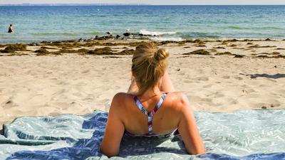 Eine Urlauberin genießt das sommerliche Wetter am Ostseeufer in Timmendorfer Strand.