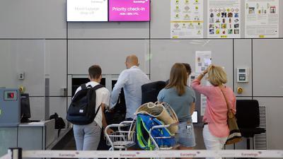Fluggäste geben im Abflugbereich des Flughafens von Palma de Mallorca am Eurowings-Schalter ihre Koffer ab.