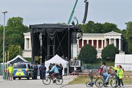 """Radler fahren über die Theresienwiese, während im Hintergrund Polizisten vor der Bühne stehen. Unter dem Motto """"#aussteigen"""" finden eine Demonstration und eine Fahrradsternfahrt gegen die Internationale Automobil Ausstellung (IAA) statt."""