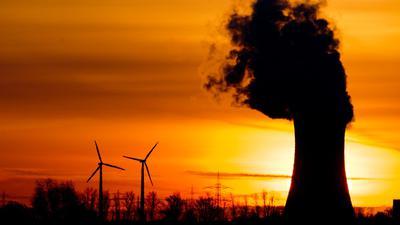 Zwei Windräder und ein Kohlekraftwerk im Licht der aufgehenden Sonne.
