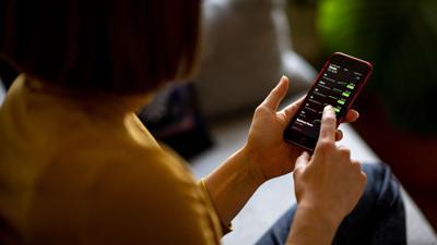 Eine jungeFrau  verfolgt die Aktienkurse mit ihrem Smartphone.