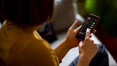 Eine Frau beobachtet mit ihrem iPhone die Aktienkurse in der App Stocks.