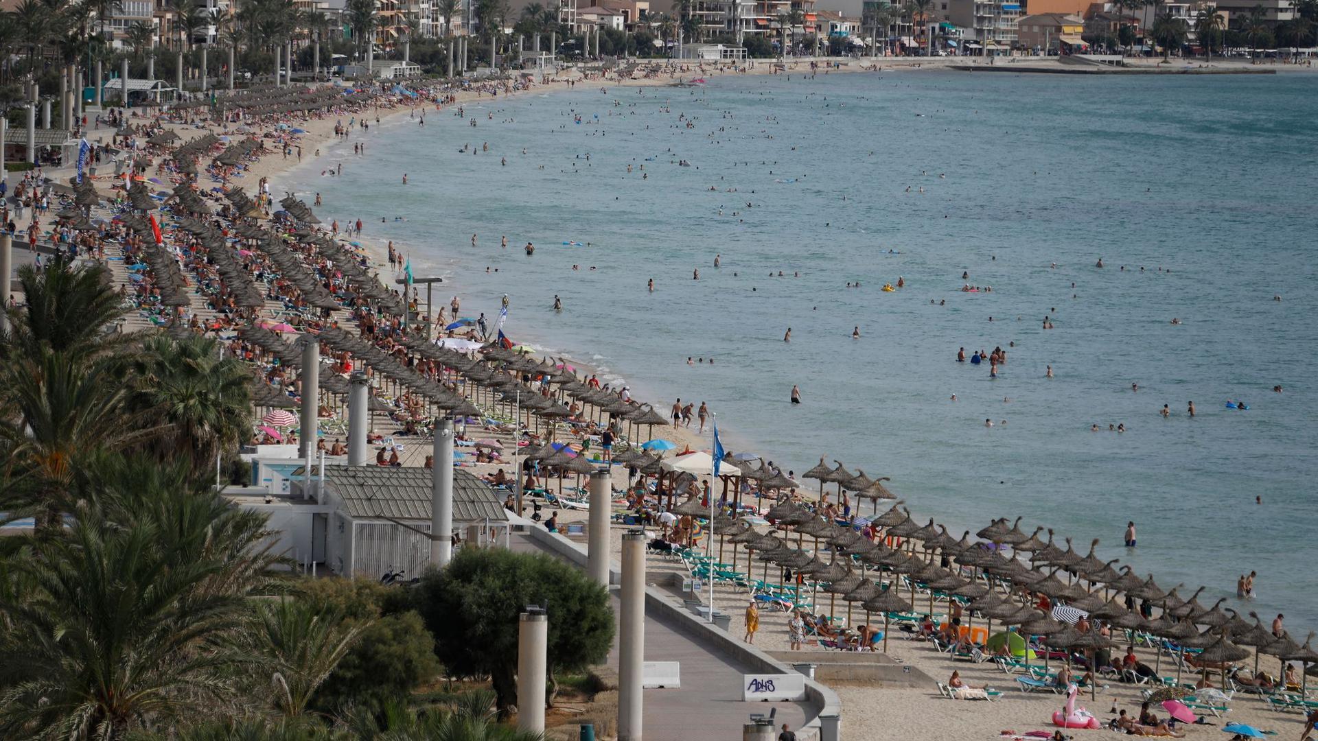 Urlauber entspannen am Strand von Arenal auf Mallorca.