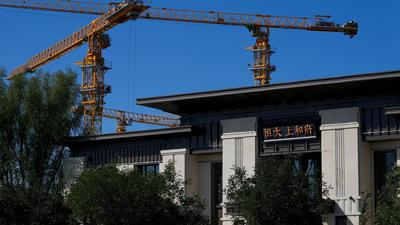 Baukräne stehen in der Nähe eines Bürogebäudes des Evergrande New Housing Development Showroom.
