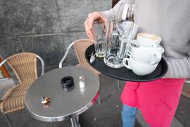 Ein Kellner räumt einen Tisch in einem Restaurant ab. Ob Minijobber auf Bezahlung pochen können, wenn ihre Arbeit während der Lockdownphasen in der Corona-Pandemie nicht gebraucht wurde, will das Bundesarbeitsgericht jetzt grundsätzlich klären.