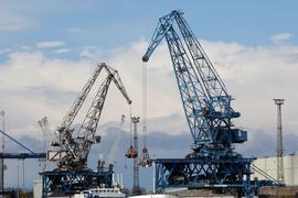 Im Seehafen an der Ostsee wird ein Schiff mit Kränen abgefertigt.