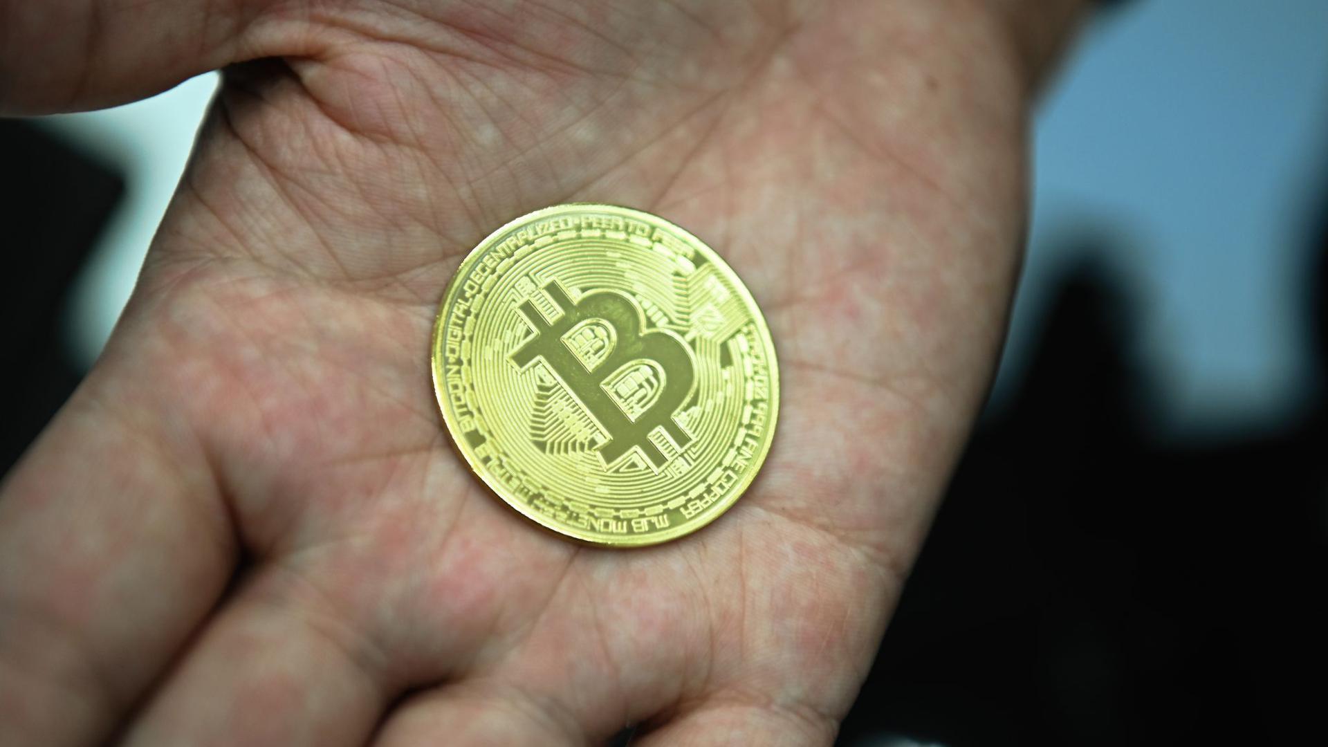 Münze mit Bitcoin-Logo: Verbraucherschützer warnen wegen der stark volatilen Kurse generell von einer Anlage in der Kryptowährung.