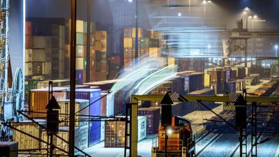 Am Containerbahnhof Frankfurt-Ost stehen am frühen Morgen hunderte Container, während im Vordergrund ein Kran einen weiteren von einem angekommenen Güterzug hinzufügt.