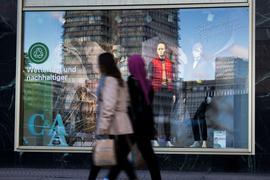 Passanten gehen an einem Schaufenster am Berliner Alexanderplatz vorbei.