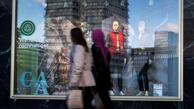 Passanten gehen an einem Schaufenster der Modekette C&A am Berliner Alexanderplatz vorbei.