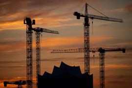 Die Kräne verschiedener Baustellen in der Hamburger Hafencity zeichnen sich im Sonnenuntergang vor der Elbphilharmonie ab.