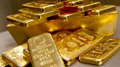 Goldbarren in unterschiedlicher Größe liegen bei einem Goldhändler in einem Tresor.