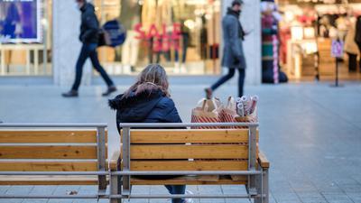 14.12.2020, Niedersachsen, Hannover: Eine junge Frau sitzt mit ihren Einkäufen auf einer Bank in der Innenstadt. Zum Eindämmen der sich weiter stark ausbreitenden Corona-Pandemie wird das öffentliche und private Leben in Deutschland ab dem 16.12.2020 drastisch heruntergefahren. Foto: Ole Spata/dpa +++ dpa-Bildfunk +++