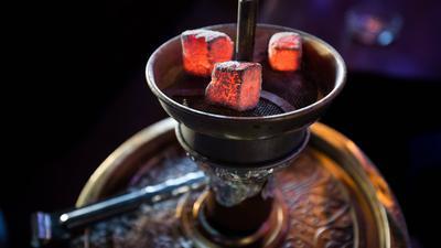 Glühende Kohle liegt auf einem Metallsieb über dem Tabak im Kopf einer Wasserpfeife in einer Shisha-Bar.