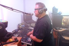 Mann mit Brille am Mischpult und am Mikrofon.