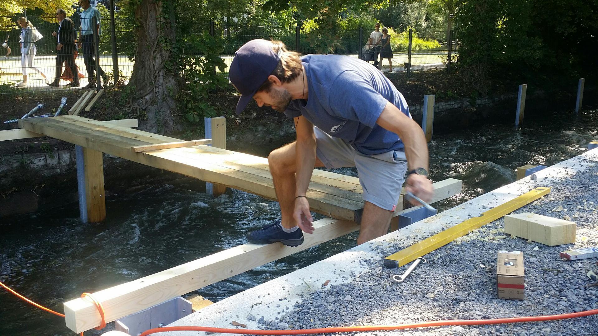 Steffen Rose, Vorsitzender von Black Forest Wave, bei der Montage der Holzkonstruktion für den Zugang zum Surfvergnügen im Metzelgraben in Pforzheim. Werkzeug hat er in der linken Hand und neben sich. Er steht auf einem Holzbalken über dem Wasser.