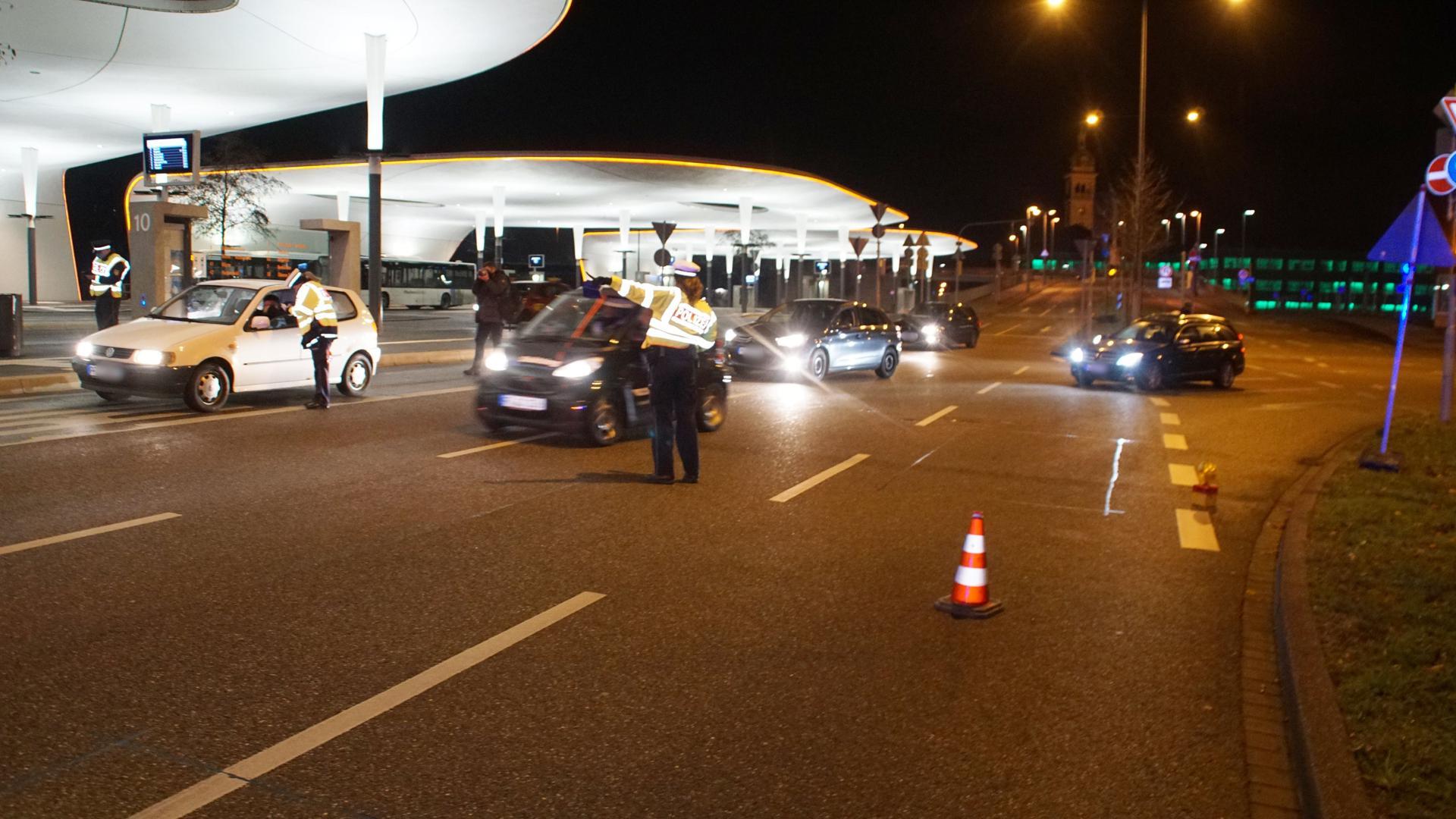 Polizisten halten am Pforzheimer Hauptbahnhof in der Nacht ein Auto an.