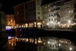 Lichtpunkte des Pforzheimer Nachtlebens spiegeln sich im Wasser an der Enz-Arkade.