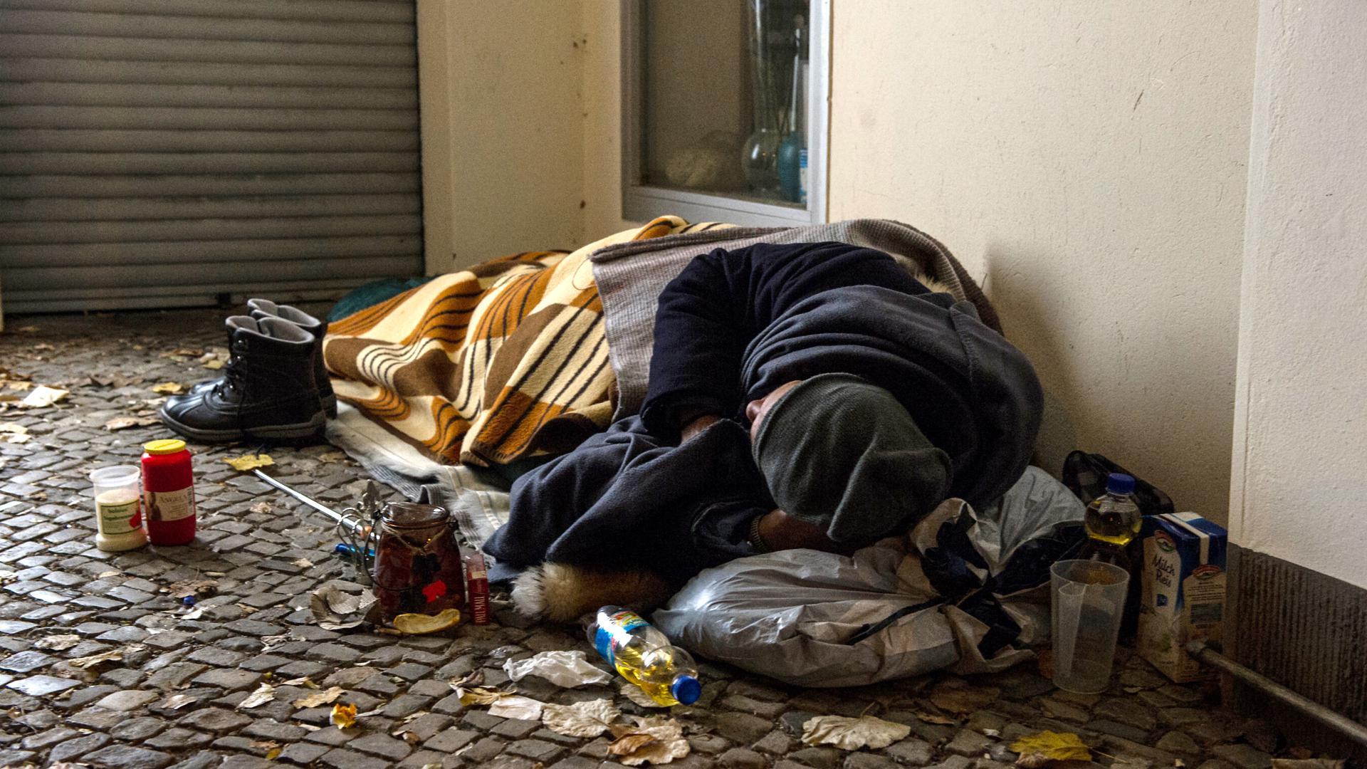 Ein Obdachloser liegt in einem Hauseingang
