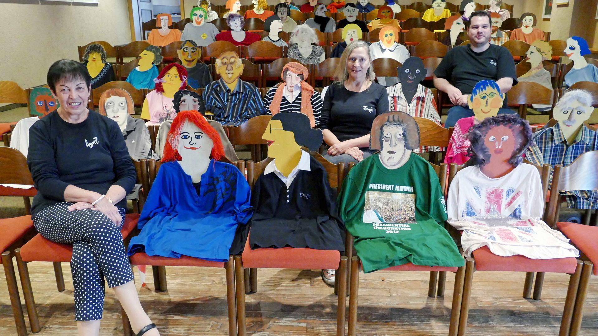 Mehrere Stühle sind in Reihen aufgestellt, auf ihnen sitzt das Publikum: Zwischen mehreren Papp-Figuren sitzen drei echte Menschen, einige Stühle bleiben auch frei.