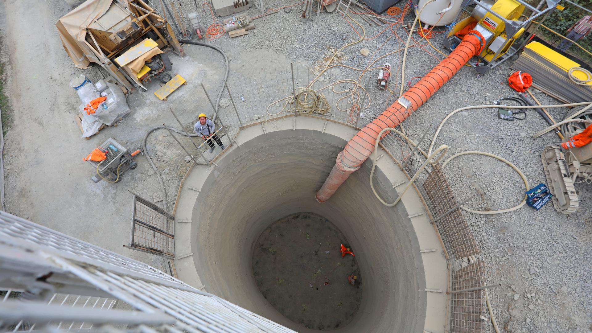 Der Entlüftungsschacht für den Arlingertunnel entsteht. Das Loch ist derzeit gut zehn Meter tief, weit unten stehen zwei Männer darin. Oben ist das Loch abgezäunt, Baugeräte und weitere Arbeiter stehen darum herum.