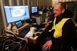 Ein Mann sitzt in gelber Warnweste vor einem Computer.