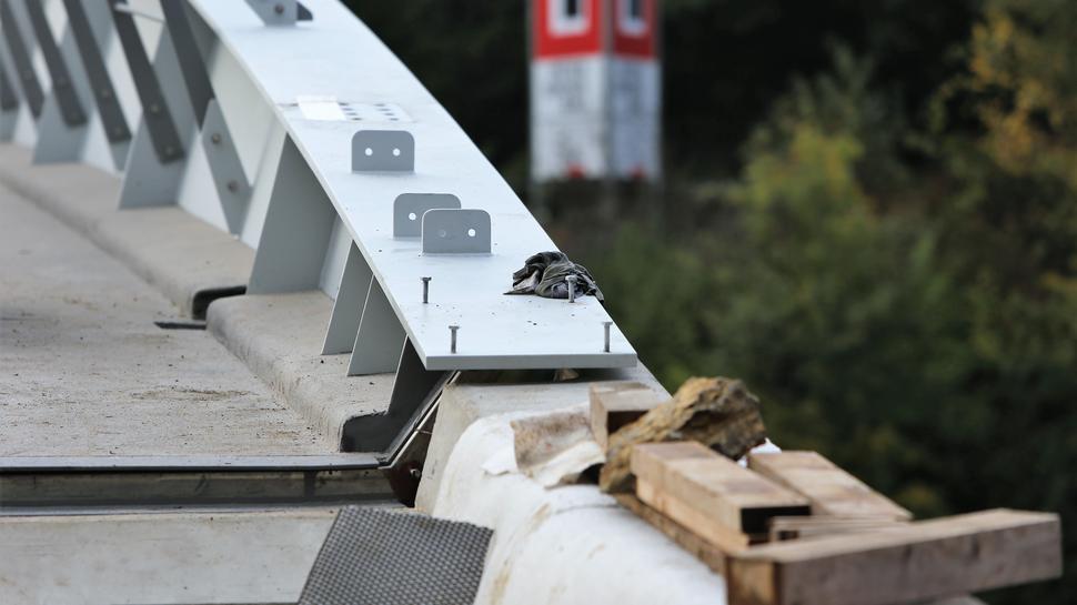 Das Geländer muss teilweise noch verschraubt werden, Werkzeug liegt noch herum. Die Brücke ist noch längst nicht freigegeben.
