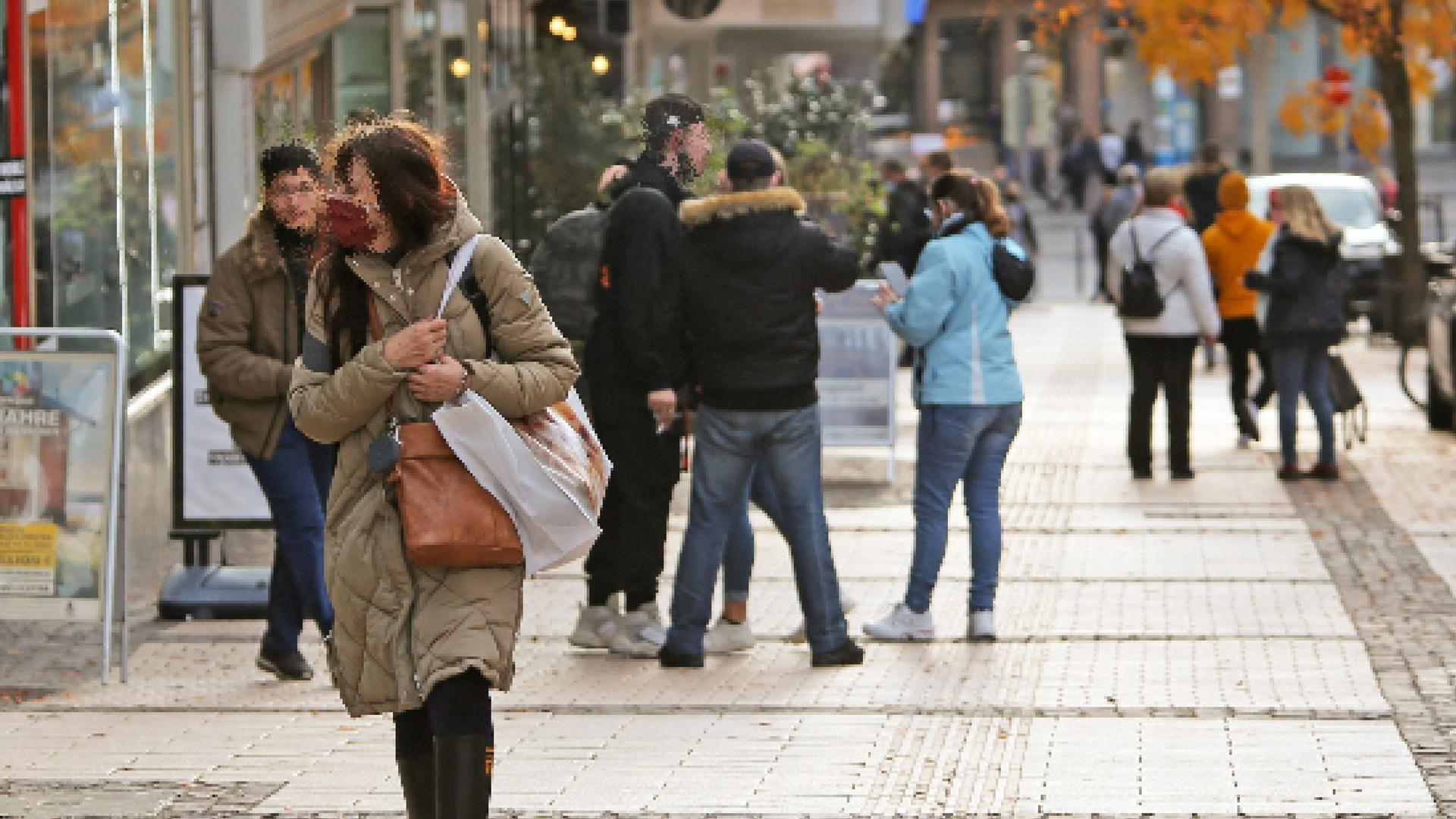 Eine Frau läuft auf einem breiten Gehweg, sie trägt einen Mundnasenschutz. Im Hintergrund Jugendliche teils ohne Mundnasenschutz.