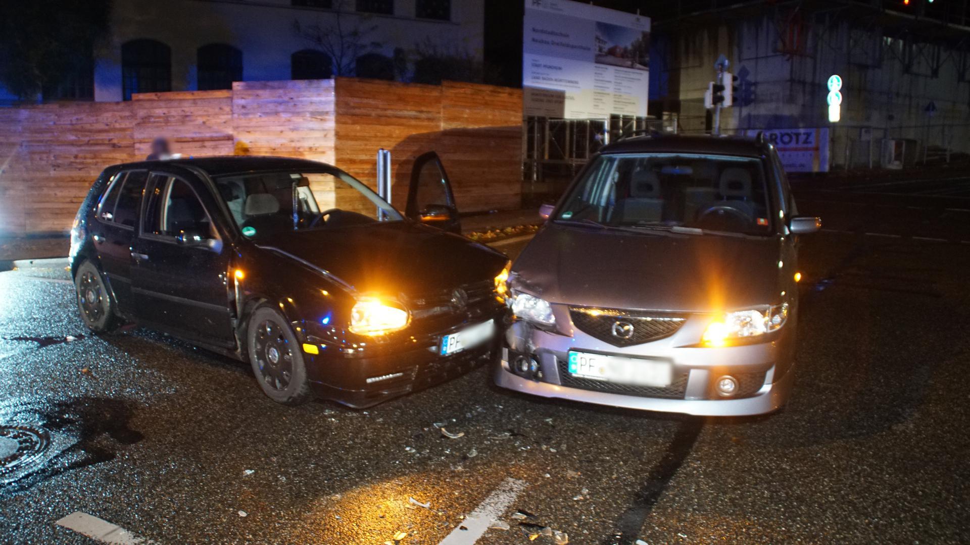 Zwei PKW stehen demoliert nebeneinander auf der Straße.