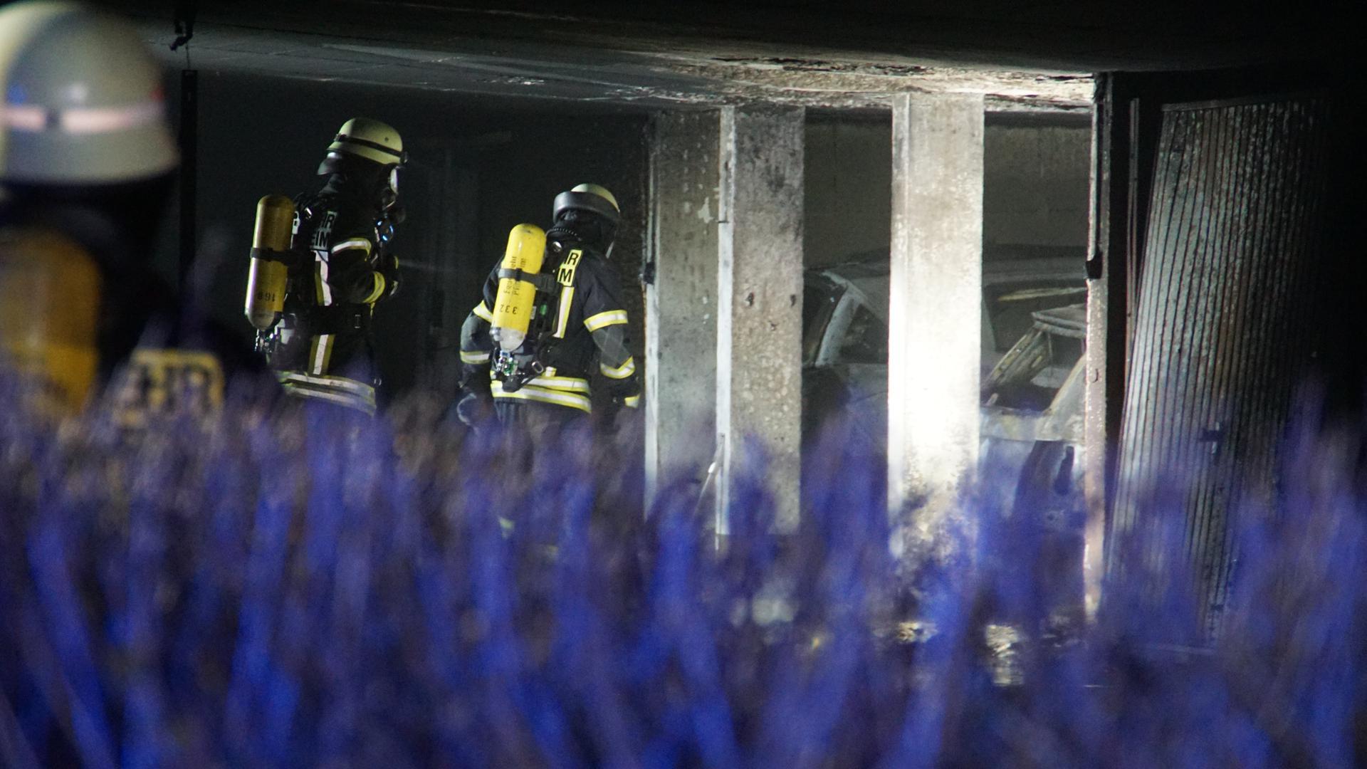 Feuerwehrleute gehen in die verrußte Tiefgarage, in der drei Autos bei einem Brand zerstört wurden.