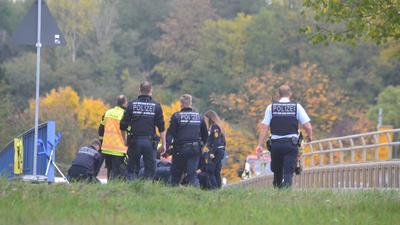 Polizisten stehen auf der Autobahnbrücke B294/Bauschlotter Straße und A8, man sieht sie von hinten.