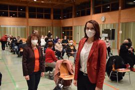 Zwei Frauen stehen vor mehreren Menschen in einer Halle.