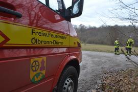 Feuerwehrfahrzeug der Freiwilligen Feuerwehr Ölbronn-Dürrn, dahinter stehen zwei Feuerwehrleute.