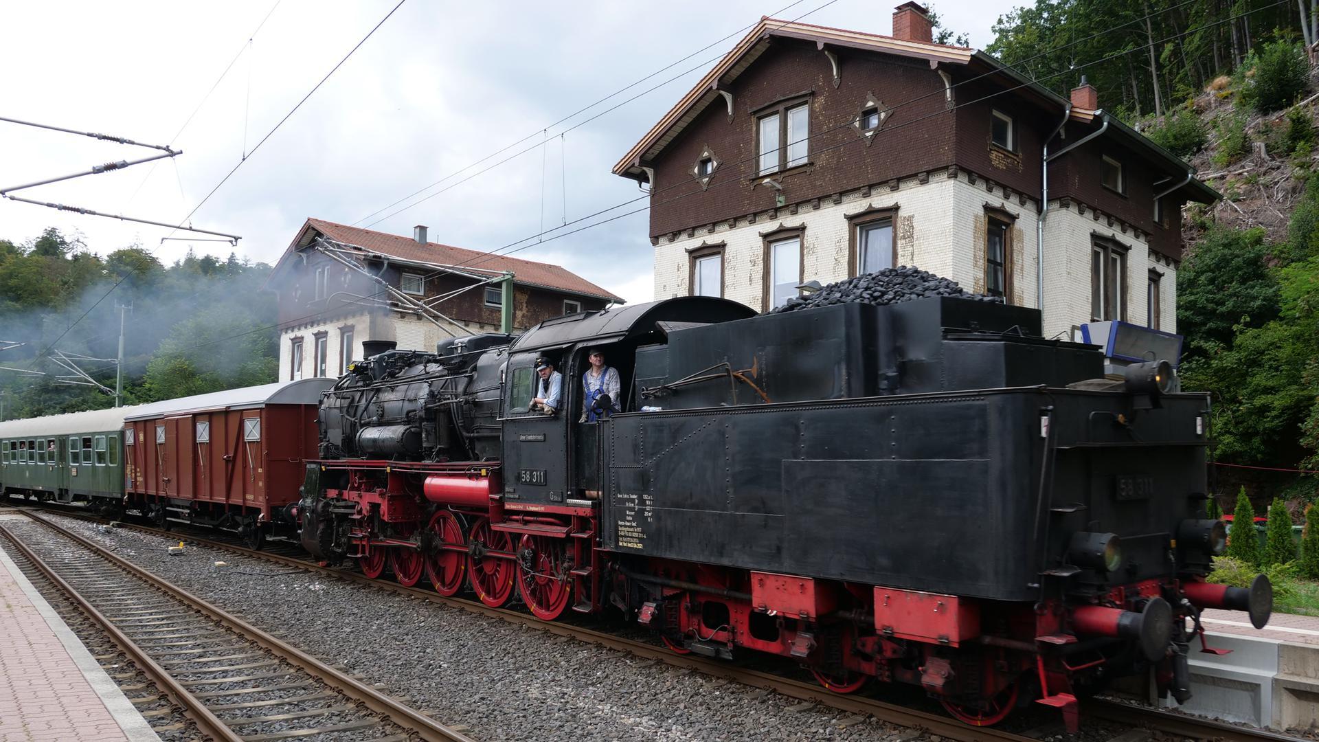 EIne Dampflokomotive fährt an Häusern vorbei.
