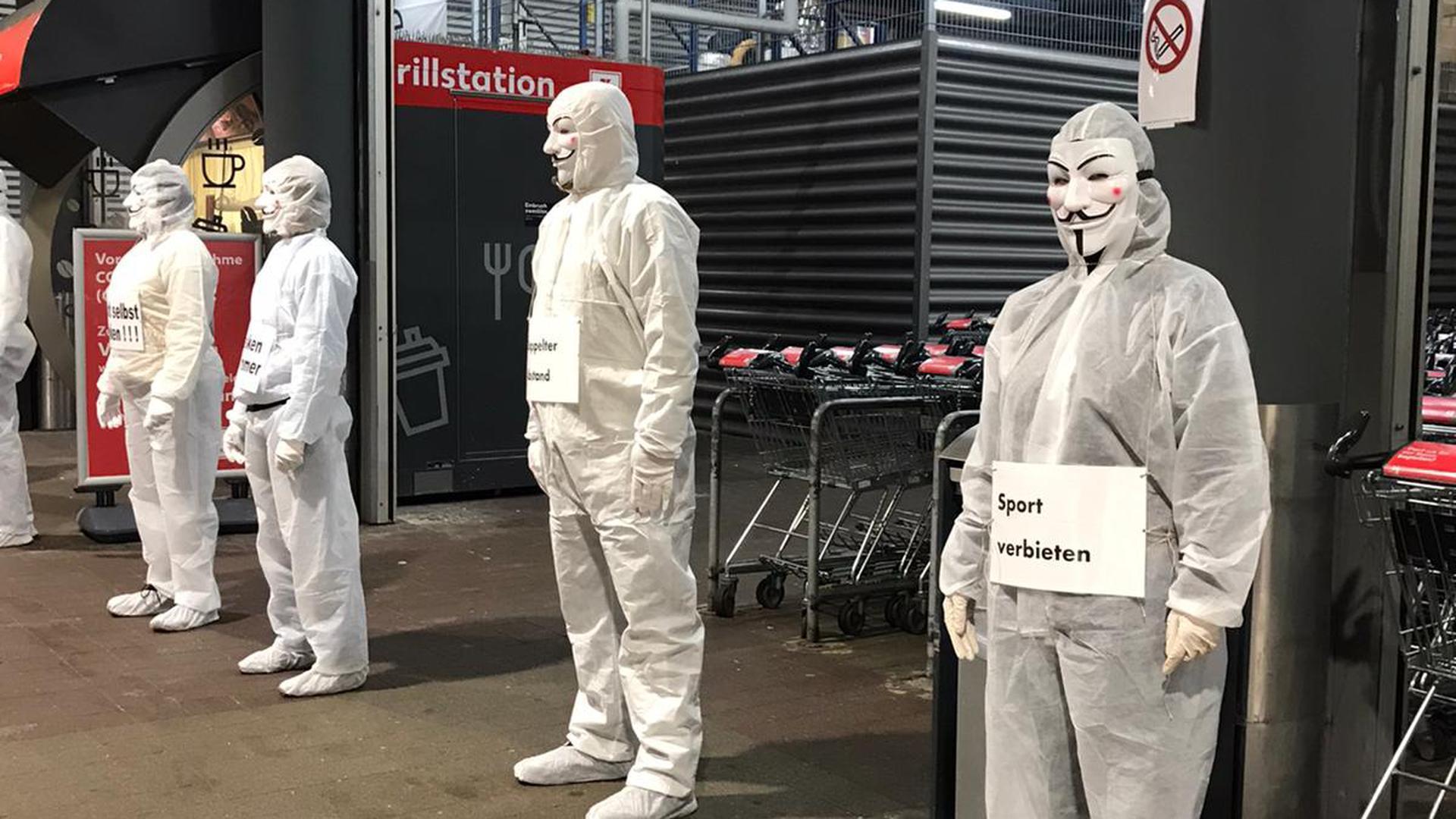 Bei einer Protestaktion in Pforzheim auf der Wilferdinger Höhe stehen einige Menschen ganz in weiß gekleidet mit Masken vor der Kaufland-Filiale.